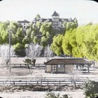 Lantern slide. A washed-out looking view of a clearing with a few shrubs, bushes, and train depot with larger trees in the background. In the distance is the Loma Linda Sanitarium, a long building with a tower.