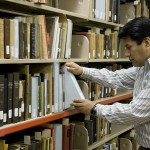 Gluder Quispe uses the compact shelving in the Center for Adventist Research vault.