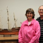 A woman and man standing with a model of a sailing vessel.